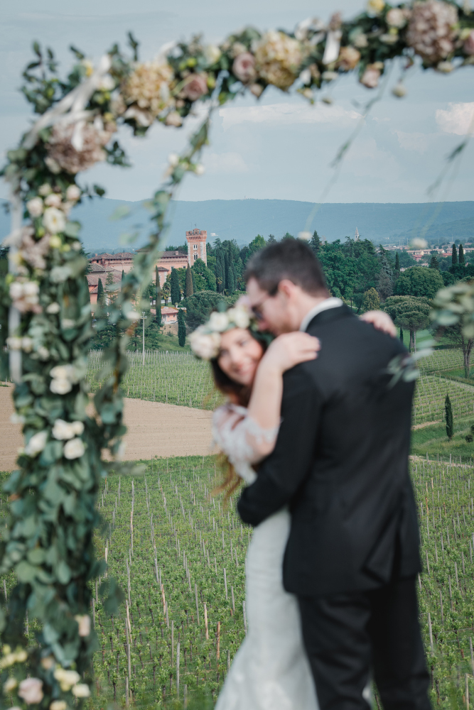 Two newlyweds embrace under a flower arch, with the Castello of Spessa in the background