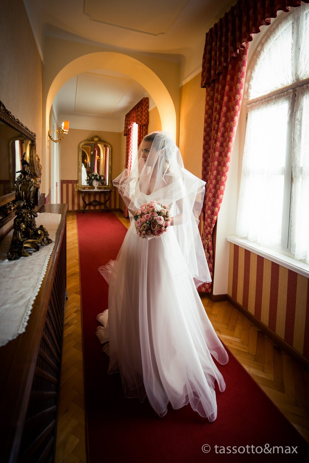 A bride with veil looking in the mirror in a corridor of an ancient castle