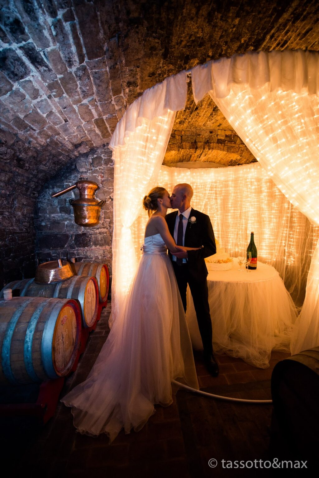 Wedding couple kissing in a medieval wine cellar, set up for the cake cut