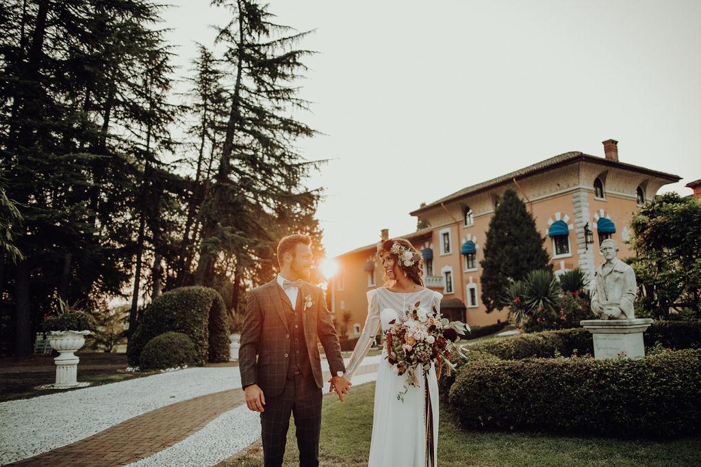 Coppia di sposi si tiene per mano al tramonto nel parco del Castello di Spessa
