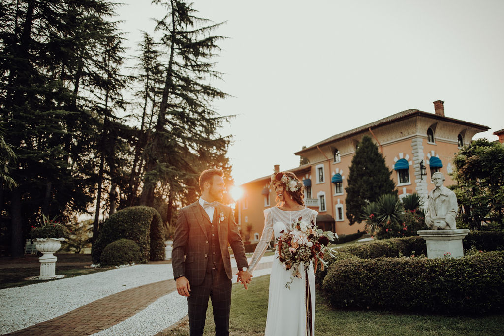 Newlyweds holding hands at sunset in the park of Castello di Spessa