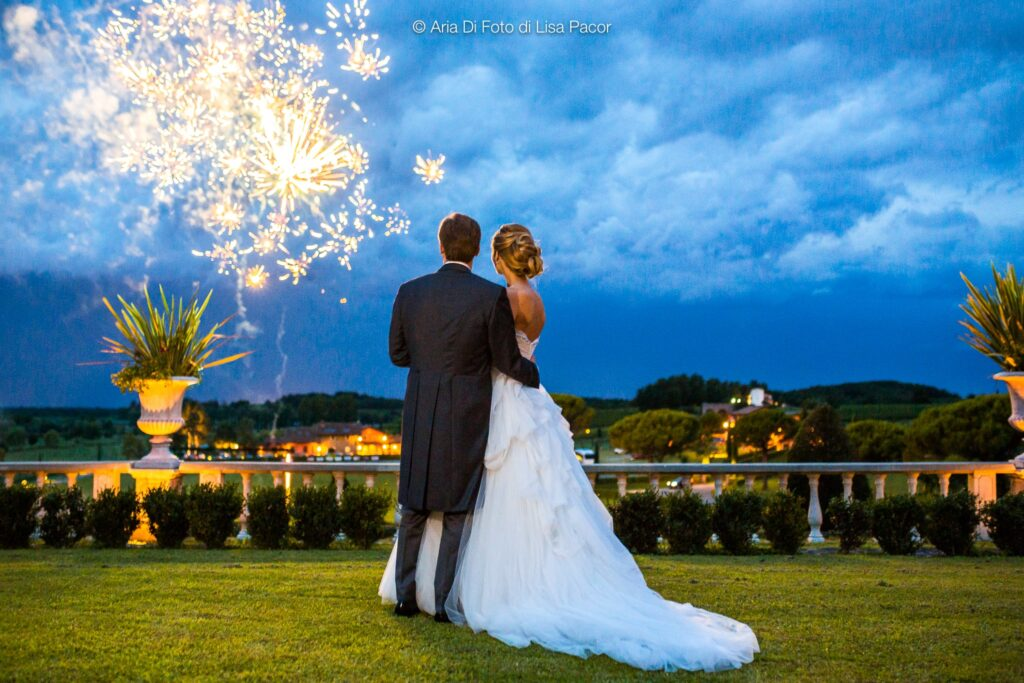 Newlywed couple watches fireworks on the horizon