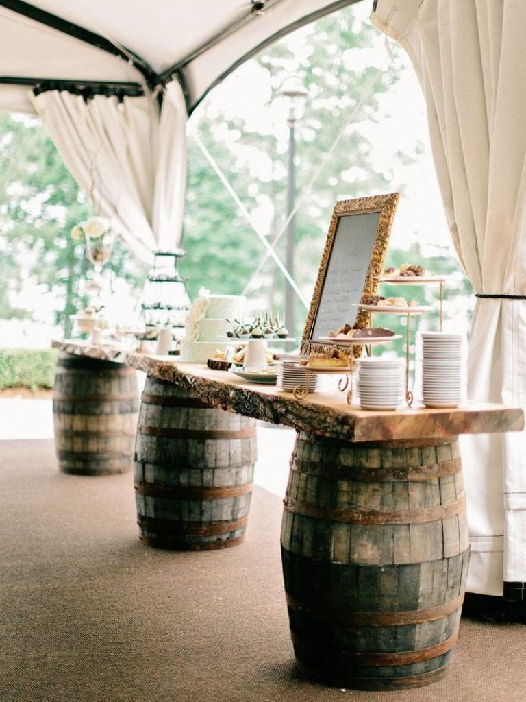 Buffet shabby chic per un matrimonio a tema vino: botti di vino utilizzate come supporto del buffet