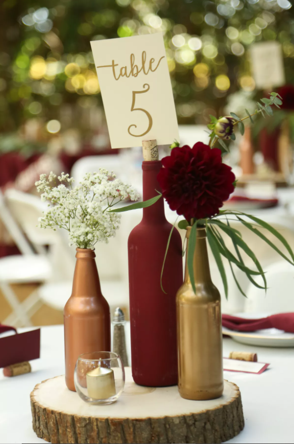 Centrotavola fatto con sezione di tronco d'albero, bottiglie colorate e fiori per un matrimonio a tema vino