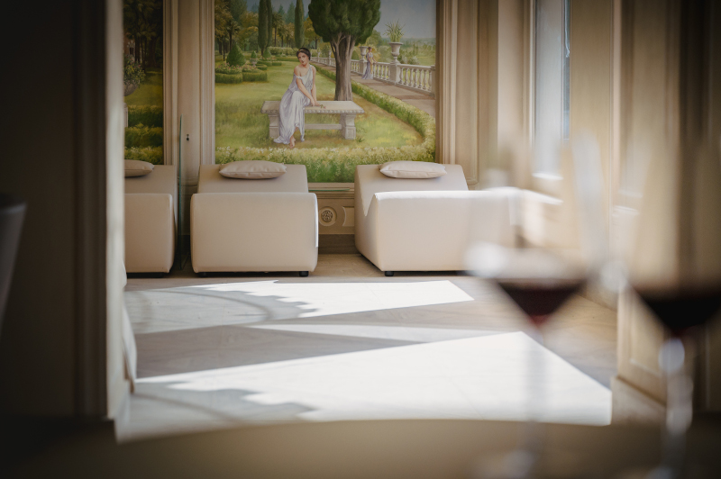 A relaxing room of a spa with wine-therapy and two glasses of red wine on the front