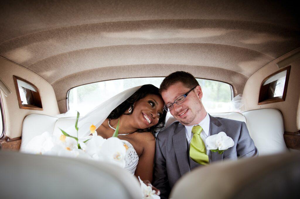 Due sposi sul retro di una macchina d'epoca dopo la cerimonia nuziale