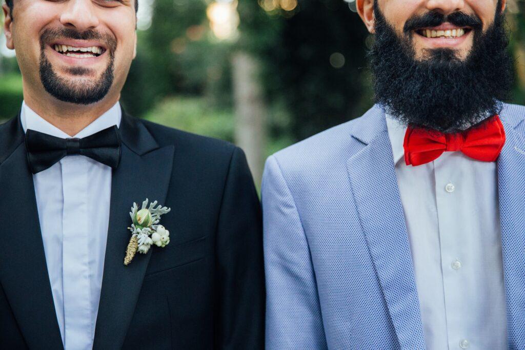 Due uomini in abito formale sorridono, primo piano