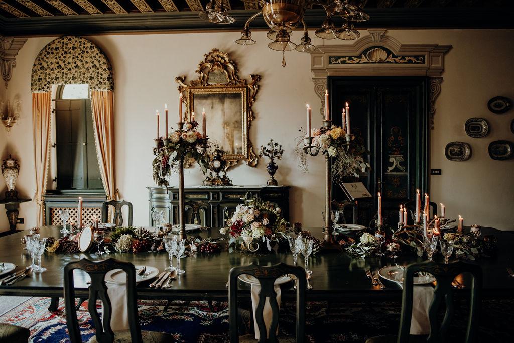 Salone interno di un castello, con tavolo imperiale allestito per un matrimonio con candelabri, fiori e mise en place