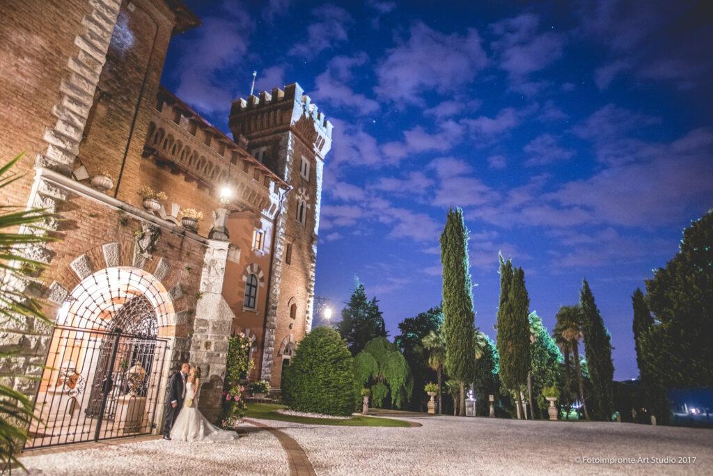 Castello medievale illuminato, di sera, con coppia di sposi che si baciano