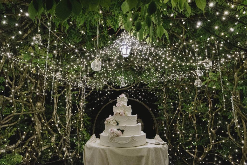 Wedding cake under a wisteria gazebo with decorative lights