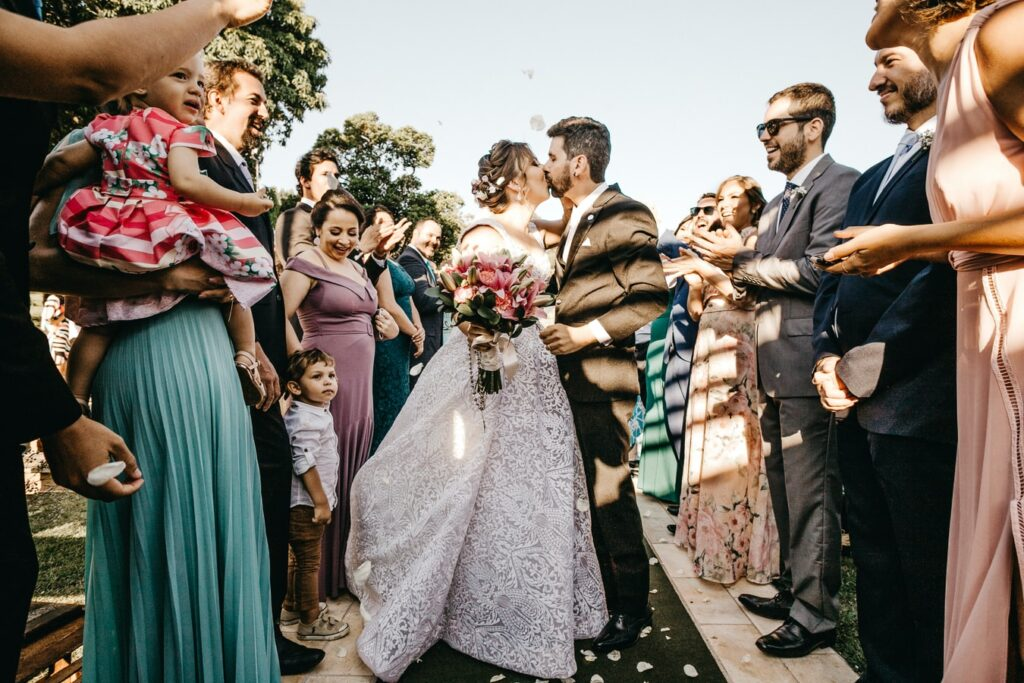 Newlywed couple kisses surrounded by guests