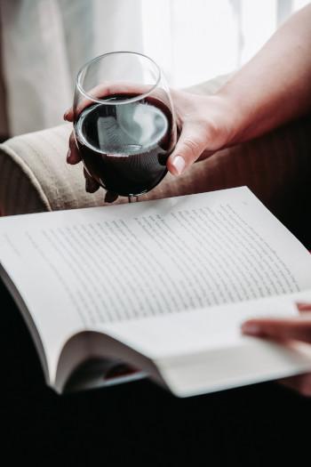 Verkostung eines Rotweins zu Hause beim Lesen eines Buches