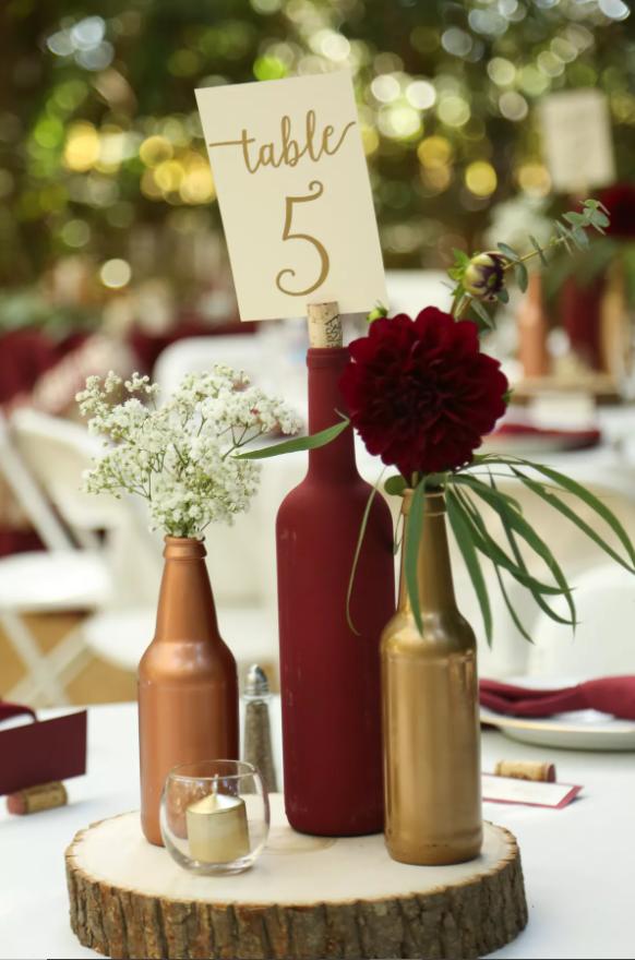 Weinhochzeitsmittelstücke: ein Abschnitt eines Baumstamms mit Flaschen, Blumen und Kerzen