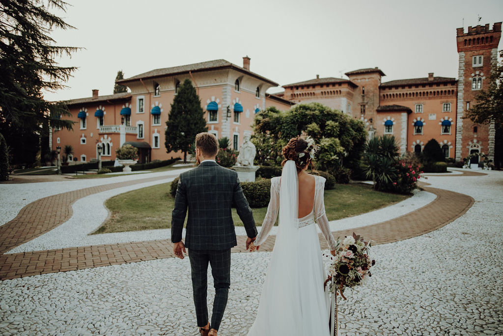 Couple holding hands from behind; in the background the Castello di Spessa