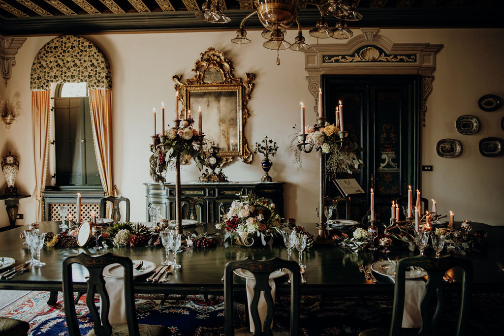Interior hall of a castle, with an imperial table set up for a wedding with candelabra, flowers and mise en place
